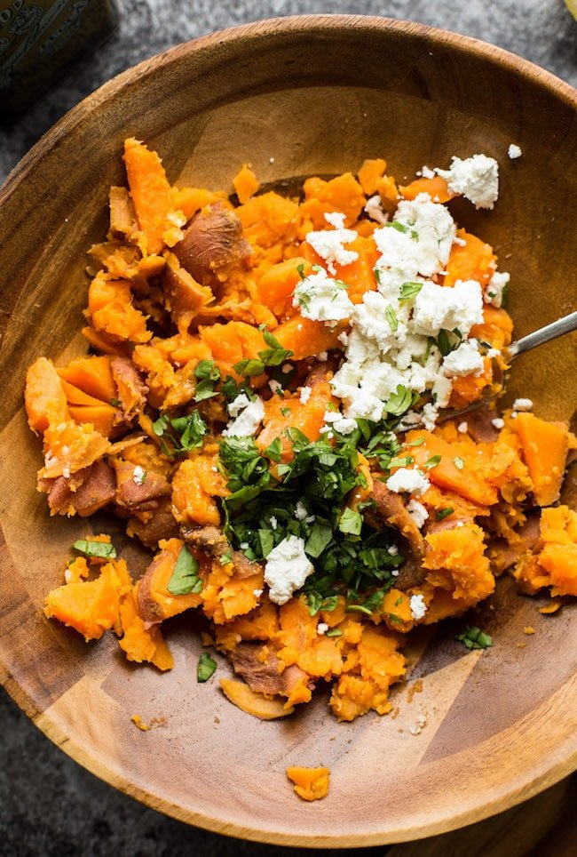 Sweet Potato Mash in a bowl topped with feta and cilantro