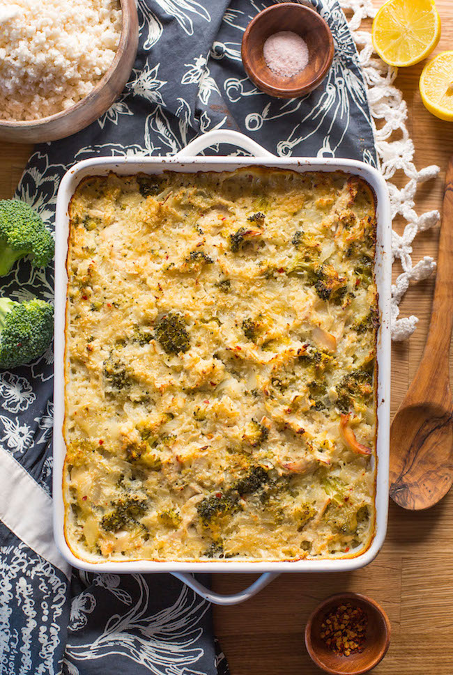 chicken broccoli cauliflower casserole on a wooden table with broccoli and spoon next to it