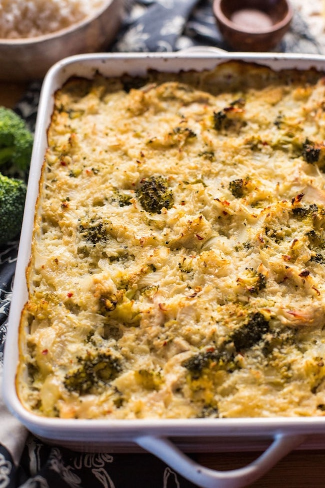 chicken broccoli cauliflower casserole on a wooden table with broccoli up close