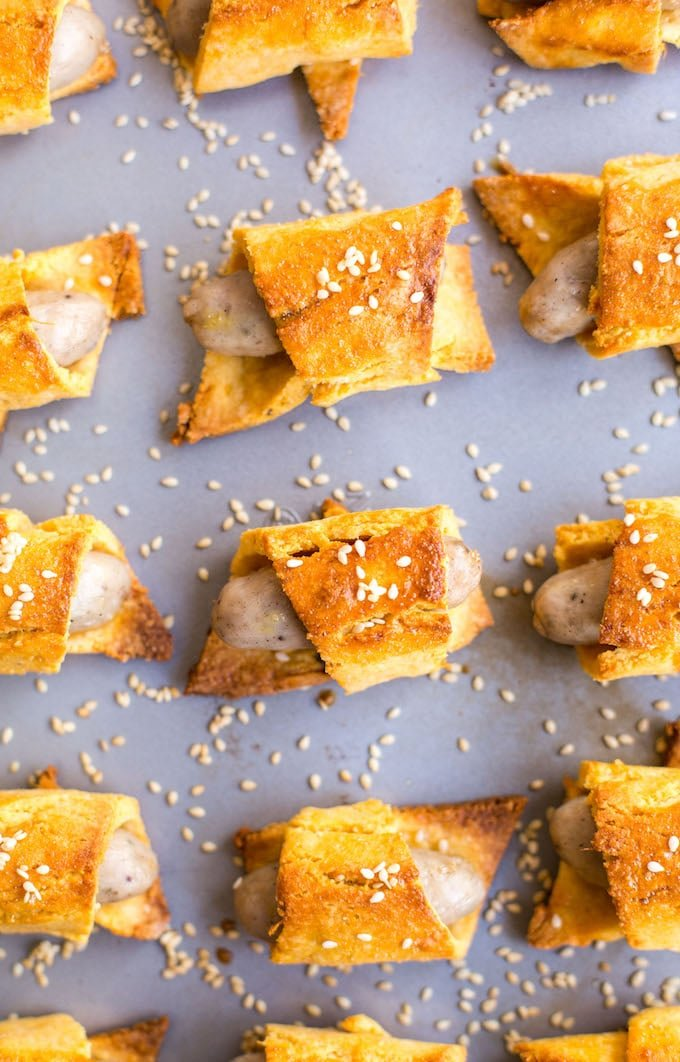 Paleo Pigs in a Blanket with sesame seeds on a baking sheet