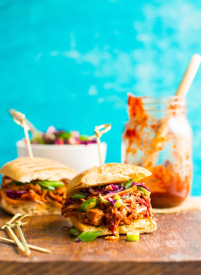 BBQ Jackfruit Pulled 'Pork' Sandwich on a cutting board with BBQ sauce in the background