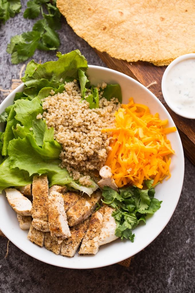 Low FODMAP Quinoa Chicken Ranch Wraps fillings - chopped grilled chicken, butter lettuce, quinoa and cheese in a bowl