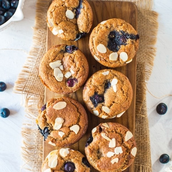 Paleo Vegan Blueberry Muffins on a wooden board topped with flaked almonds