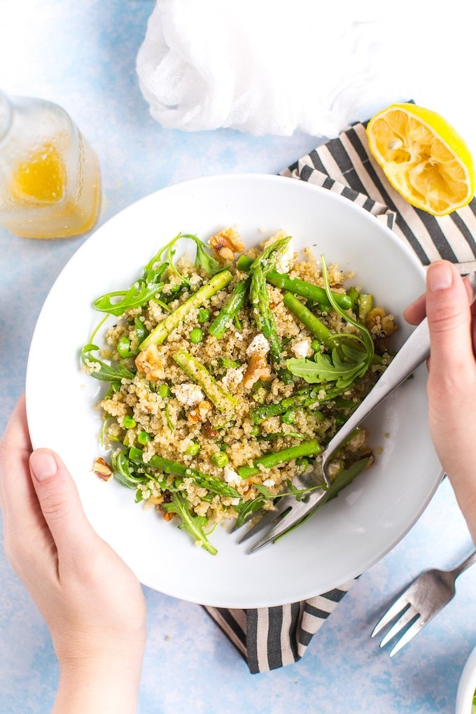 Spring Quinoa Pea & Asparagus Salad in a serving bowl held up by hands