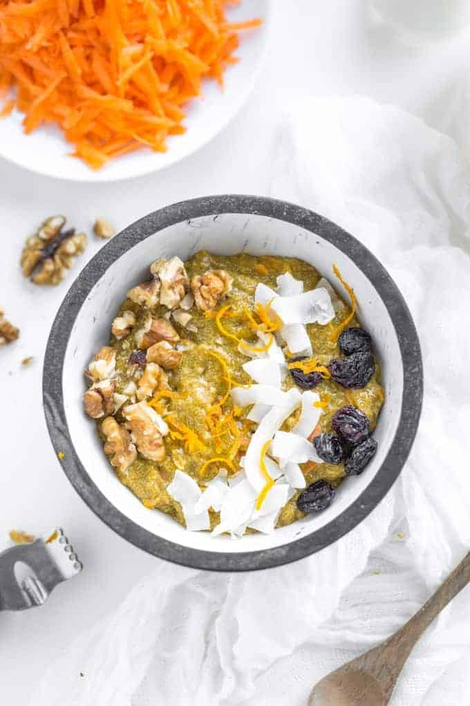Turmeric-Carrot-Chia-Pudding-in a bowl topped with fresh carrot, coconut and raisins