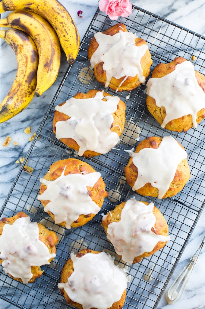 Banana Nut Scones covered in a maple glaze cooling on a wire rack with ripened bananas #gltuenfree #vegan #bananas