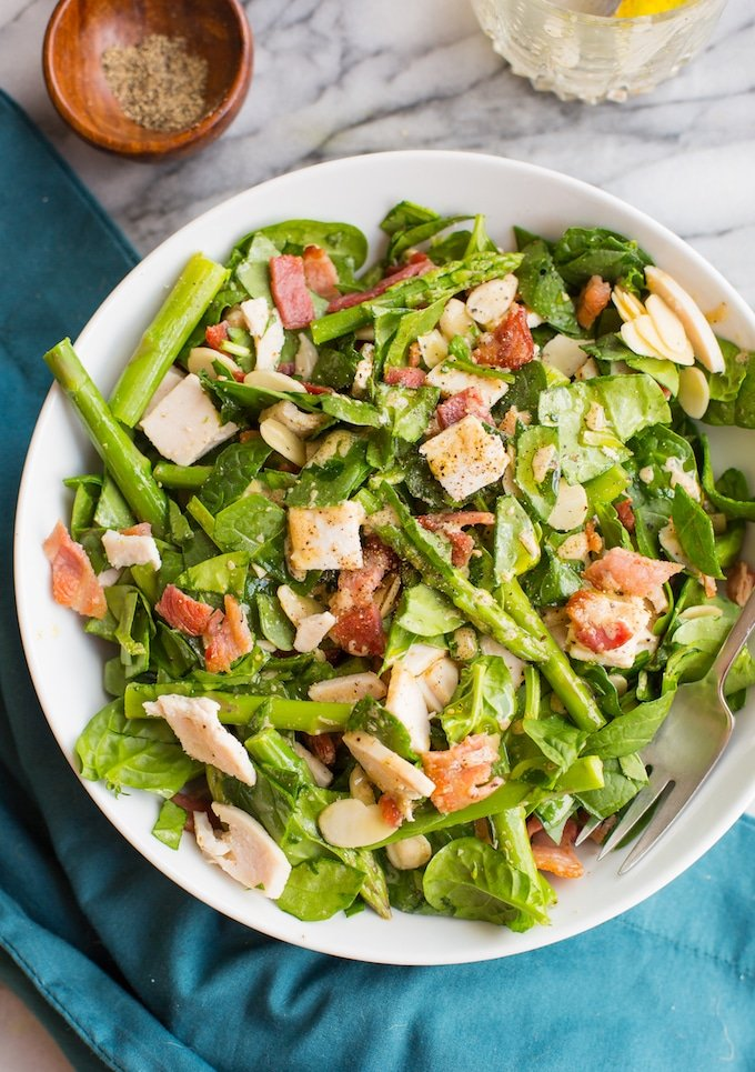 Chicken Bacon Spinach and Asparagus Salad mixed together on a bowl