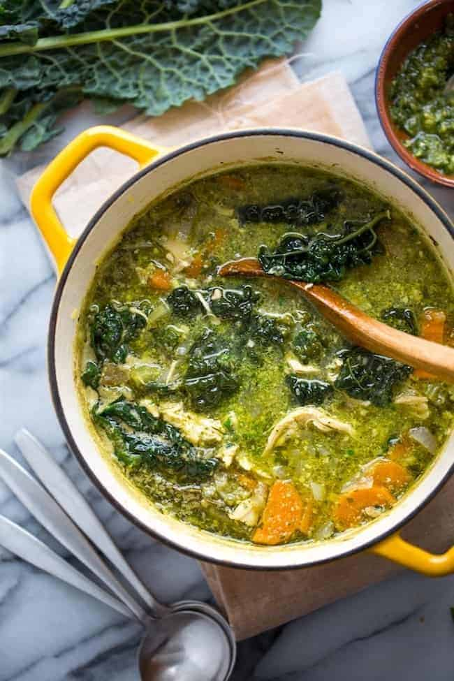 kale & chicken pesto soup in a yellow soup pot with a ladle