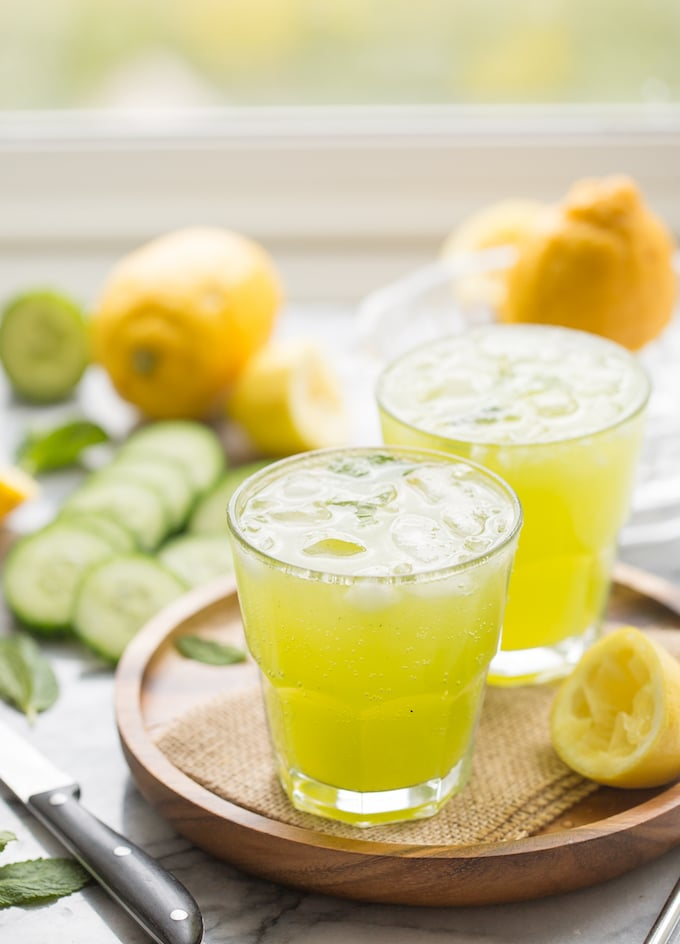 Minty Cucumber Lemonade with ice surrounded by used lemons and cucumbers
