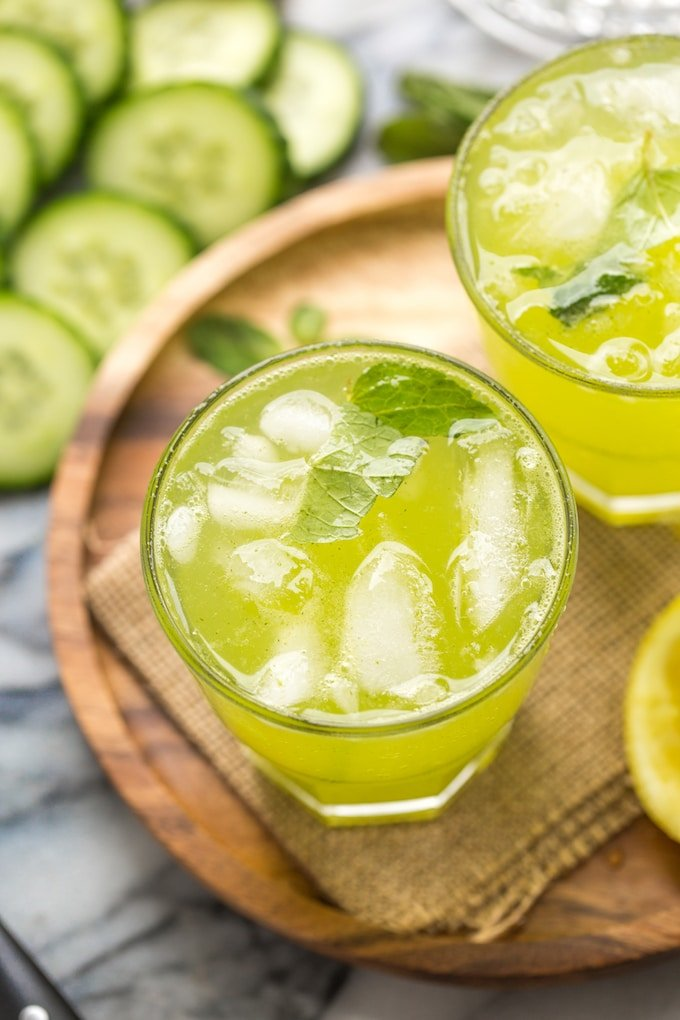 Minty Cucumber Lemonade with ice surrounded by cucumbers