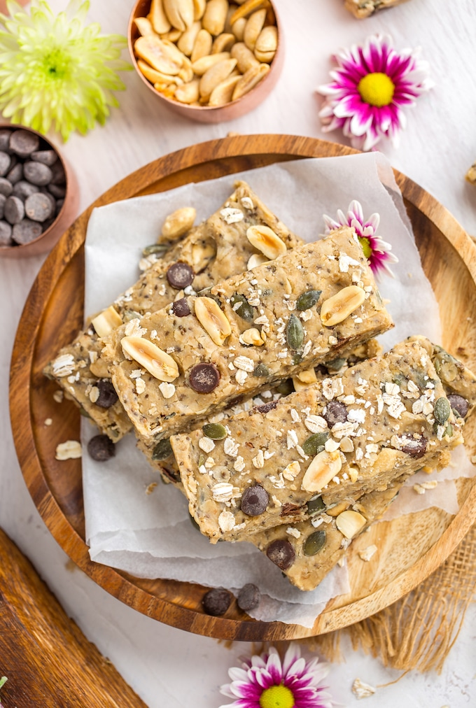 Peanut Butter No Bake Granola Bars sitting on a plate with a salted peanuts, chocolate chips and pink flowers surrounding #glutenfree #vegan