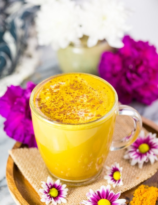 Turmeric Latte on a plate surrounded by flowers