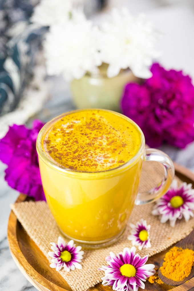 Golden Turmeric Latte with cinnamon sprinkled over the top on a plate surrounded by white and pink flowers