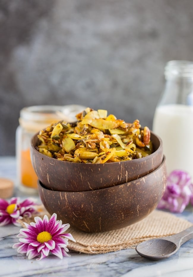 Turmeric & cinnamon spied stove top paleo granola in a cereal bowl surrounded by flowers #glutenfree #paleo #vegan