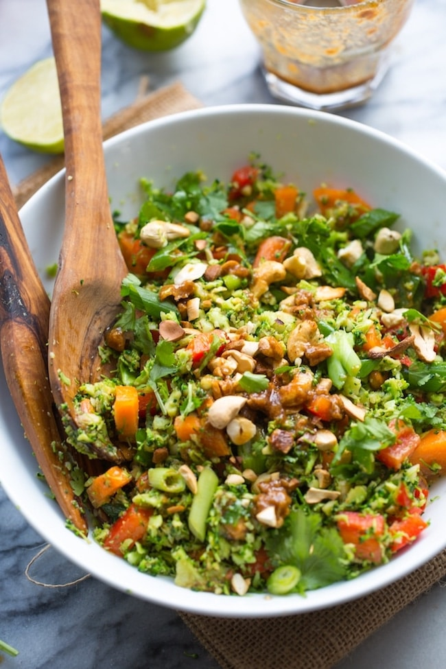 Chopped Thai Broccoli Salad in a bowl with lime on the side, springs of cilantro and cashews