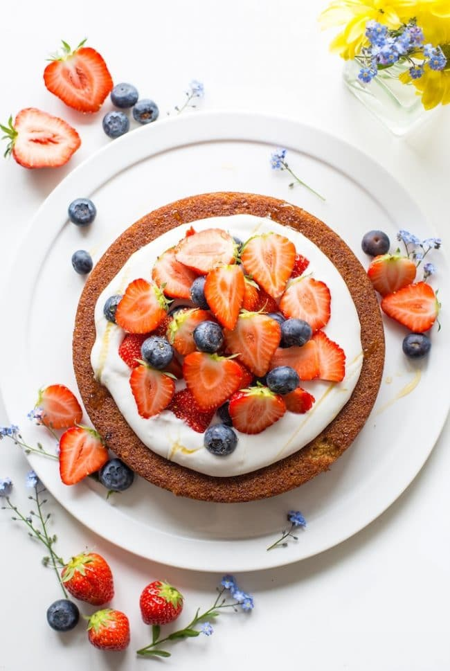 coconut flour cake topped with coconut whipped cream and berries