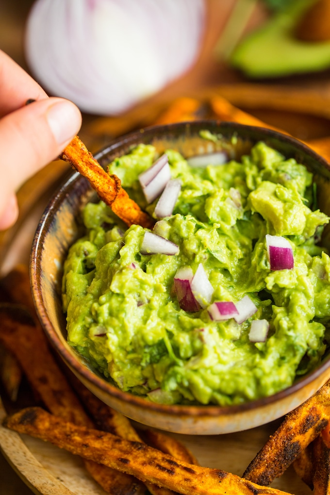 Sweet potato fry dipping into Homemade Guacamole Recipe