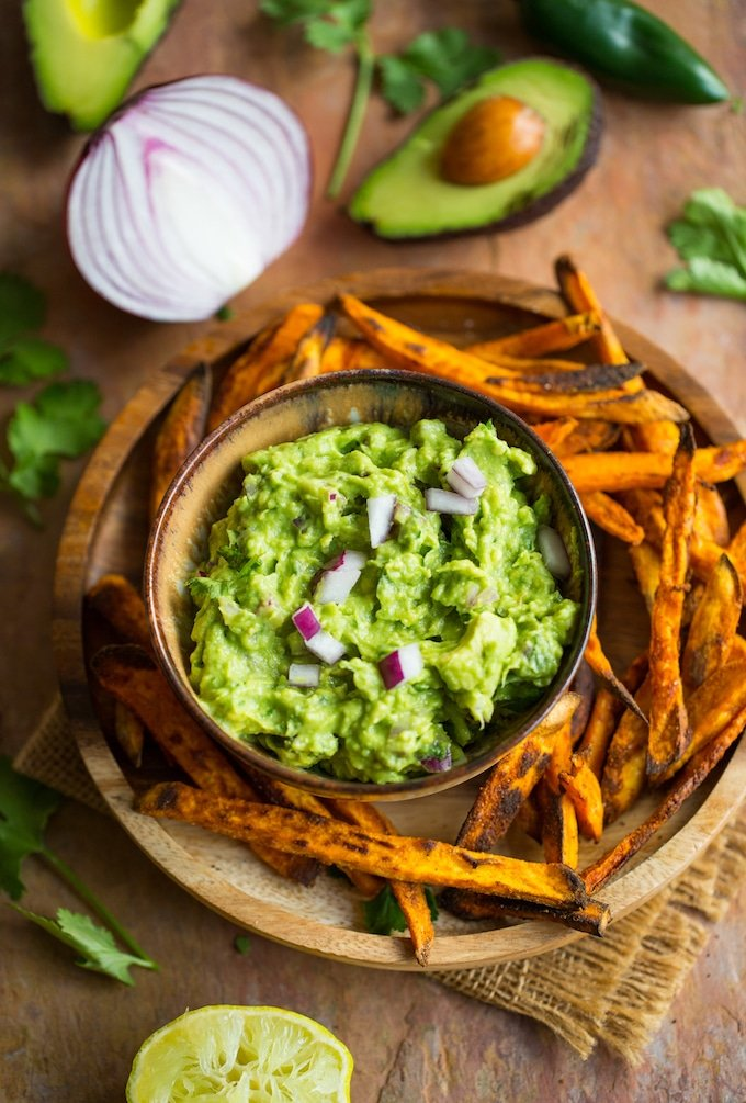 Homemade Guacamole Recipe on a plate with sweet potato fries on topped with chopped onions