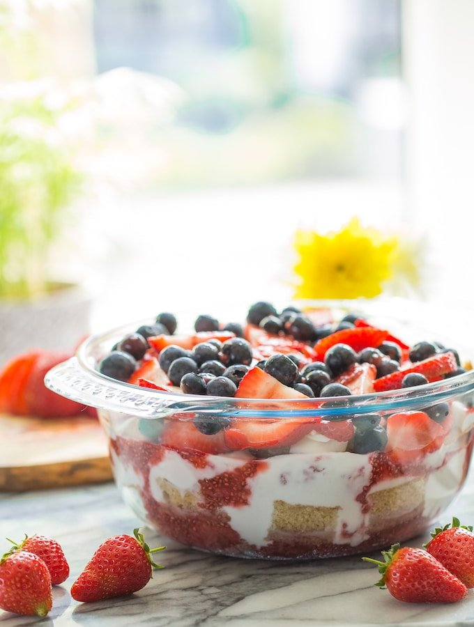 Summer Berry Coconut paleo Trifle in a bowl and topped with berries with flowers in the background