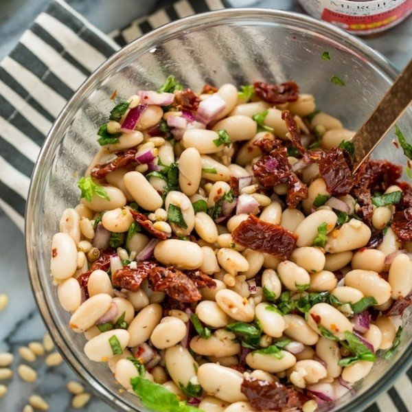 Sun Dried Tomato Cannellini Bean Salad in a salad bowl on a stripped napkin