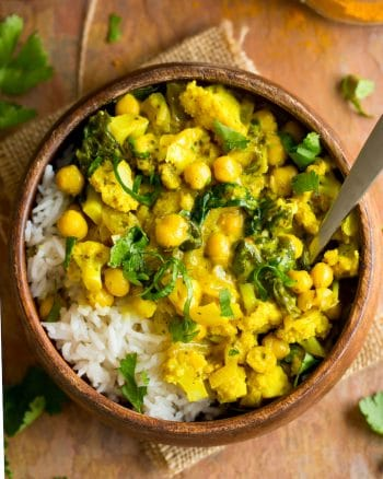 Yellow Cauliflower Chickpea Curry served over a bed of rice in a wooden bowl with a spoon