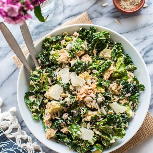 Salmon Kale Caesar Salad in a bowl with serving forks and flowers on the side