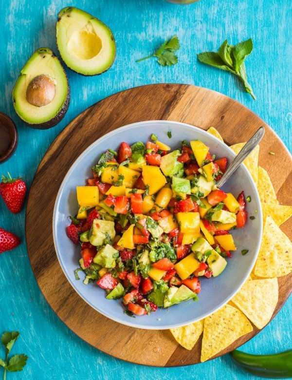 Spicy Avocado Strawberry Mango Salsa in a serving bowl with chips on a plate