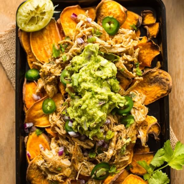 Sweet Potato Nachos on a baking sheet topped with chicken carnitas, guacamole and cilantro