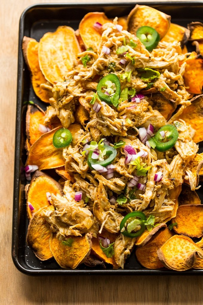 sheet potato nachos on a baking sheet topped with carnitas, chopped red onion and jalapeno