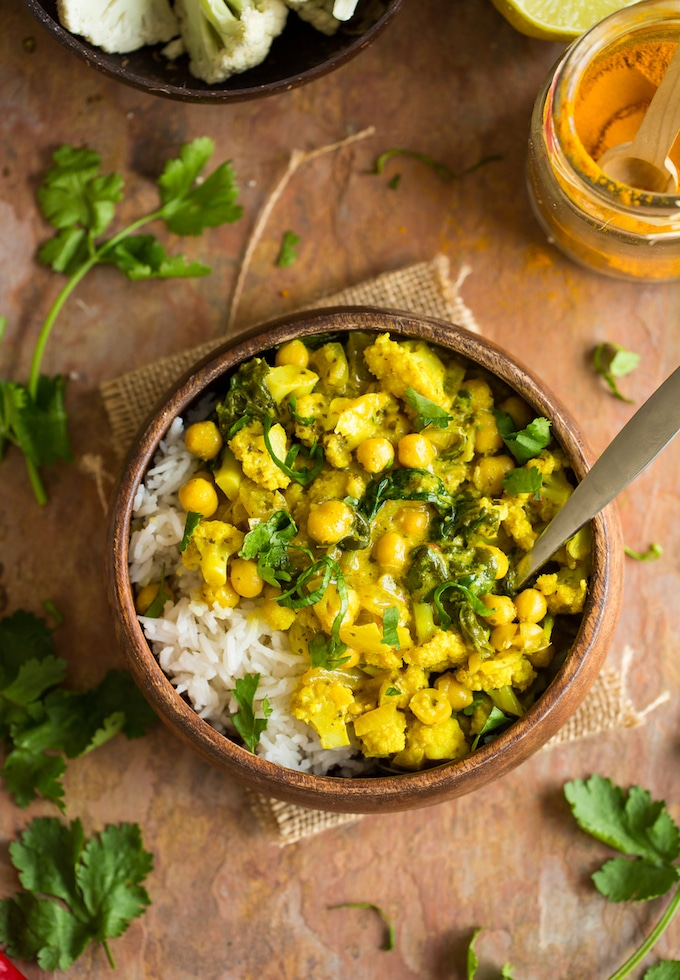 Yellow Cauliflower Chickpea Curry served over a bed of rice in a wooden bowl with a spoon surrounded by cilantro leaves