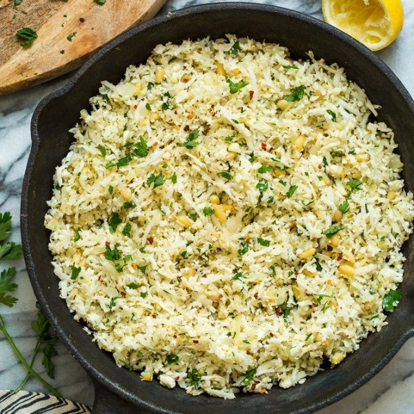 Mediterranean Cauliflower Rice in a cast iron skillet on a marble surface with lemon and parsley surrounding