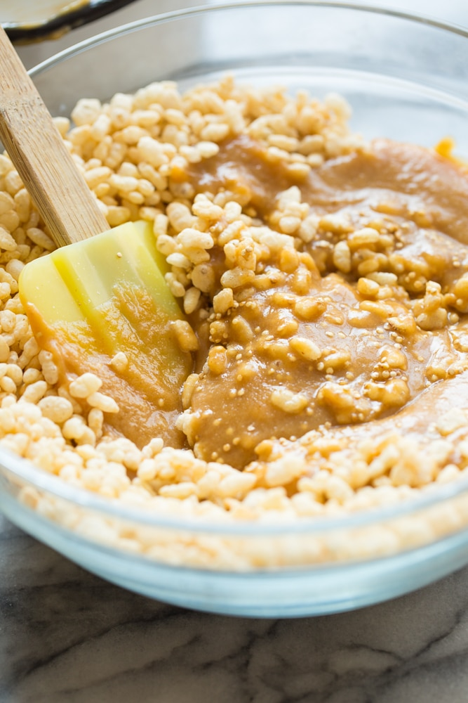 mixing together the rice crispy base of the Toasted Quinoa Peanut Butter Scotcharoos