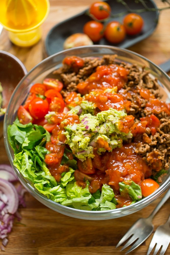 Whole30 Taco Salad in a bowl topped with salsa and guacamole