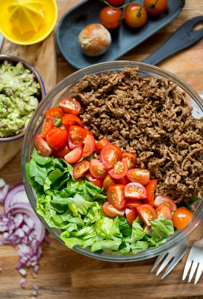 Whole30 Taco Salad: ground beef, chopped tomatoes and lettuce in a salad bowl with guacamole on the side