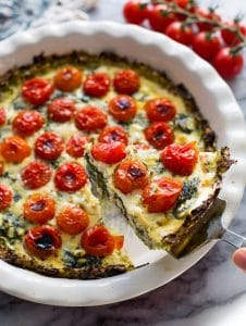 Zucchini Crust Tomato Spinach Feta Quiche in a pie plate with a slice lifted up on a spatula