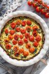 Zucchini Crust Tomato Spinach Feta Quiche in a pie plate on a marble counter top