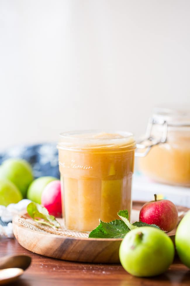 Instant Pot applesauce in a jar on a wooden plate surrounded by red and green apples