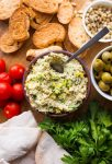green olive tapenade on a serving board surrounded by veggies, crostini and pita