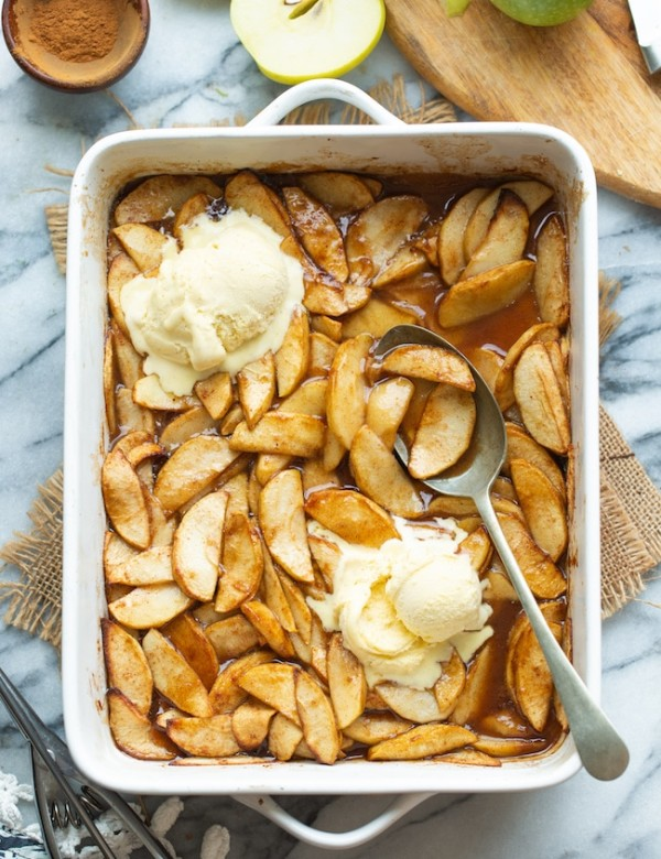 Baked Cinnamon Apples in a baking dish topped with ice cream