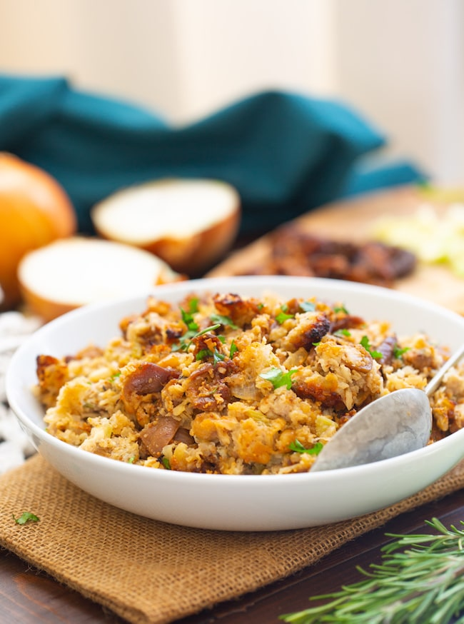 Fig & Sausage Cauliflower Stuffing in a serving bowl with a spoon