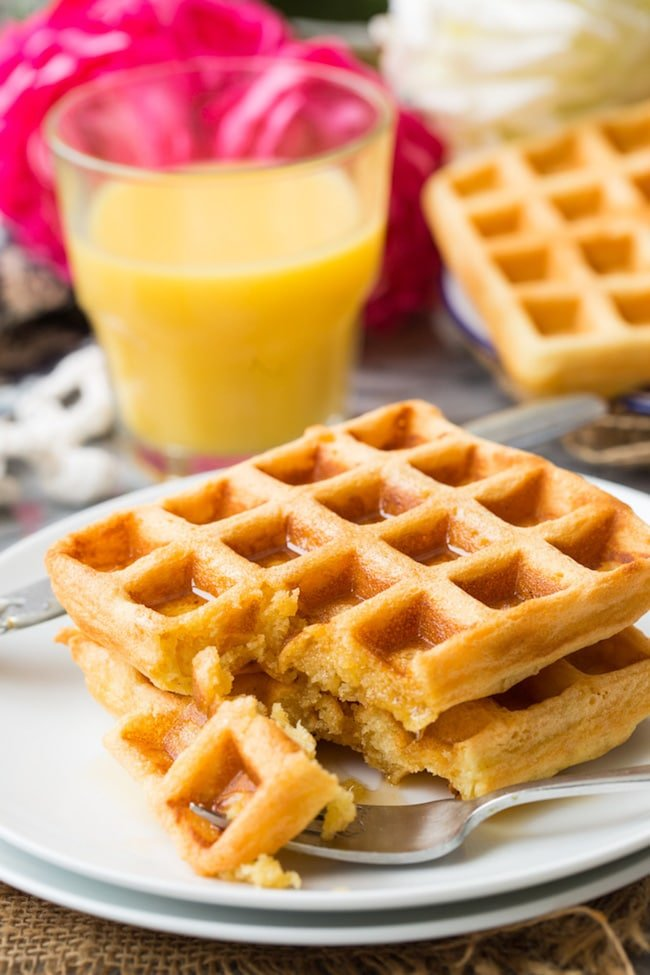 Gluten Free Waffles on a plate with maple syrup and a glass of orange juice