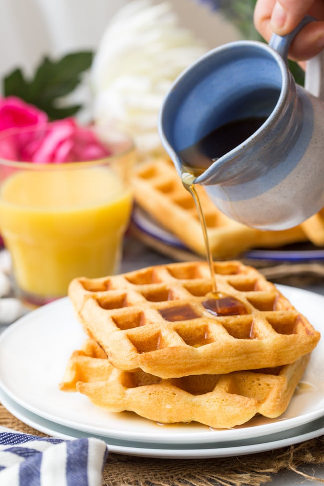 Gluten Free Waffles on a plate with maple syrup pouring over the top