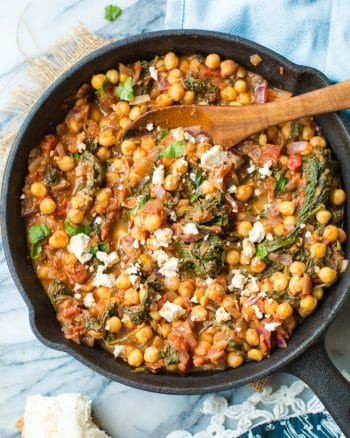 Mediterranean Chickpea Stew with Spinach & Feta in a cast iron skillet on a marble counter