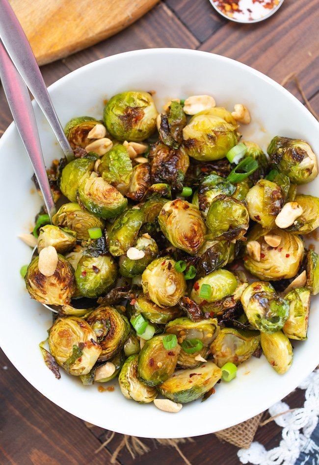 Roasted Teriyaki Brussels Sprouts topped with peanuts and spring onions in a bowl