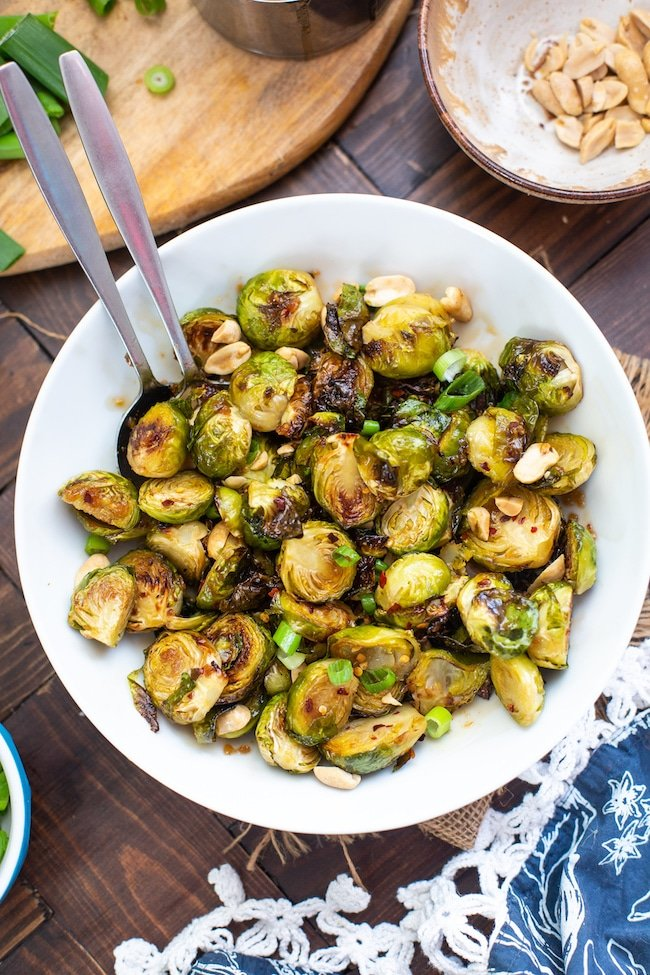 Roasted Teriyaki Brussels Sprouts in a bowl topped with peanuts and green onions