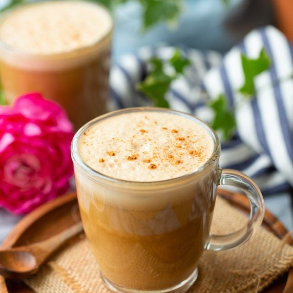 cashew butter latte on a wooden plate sprinkled with cinnamon