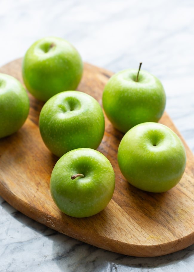 green apples on a cutting board