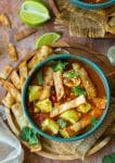 instant pot chicken tortilla soup topped with avocado and cilantro in a green bowl