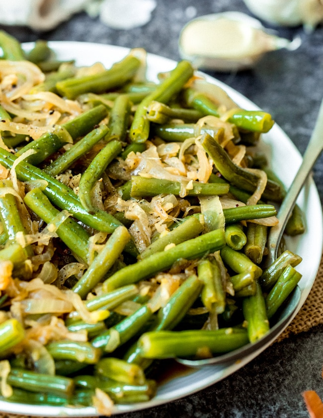 stir fried green beans on a plate with a serving spoon