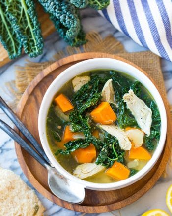 Kale & Sweet Potato Instant Pot Chicken Soup in a bowl on a wooden plate next to kale